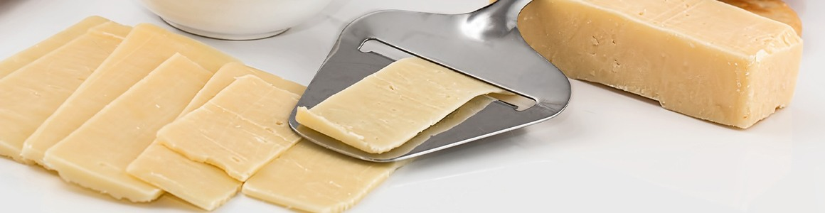 Slices of cheese with a tool to slice.