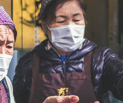 Korean women wearing masks exchanging money.