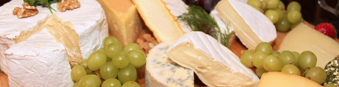 Platter of cheese wheels and grapes.
