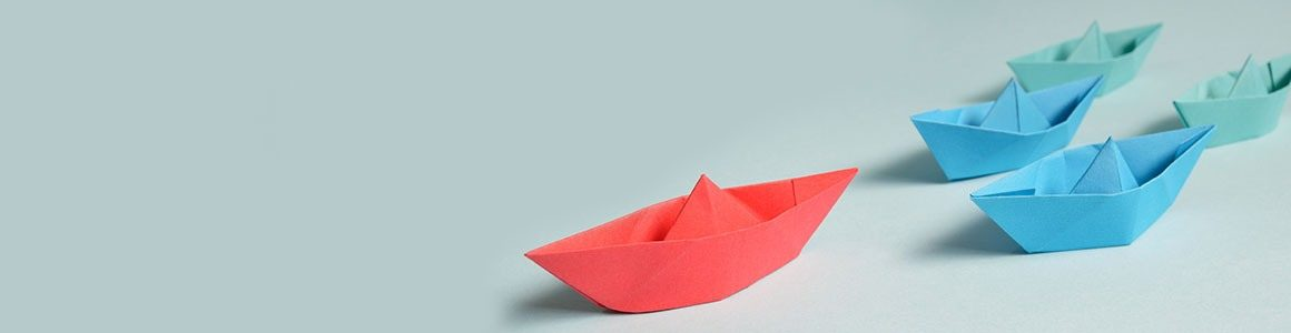 Red paper boat leading three blue paper boats