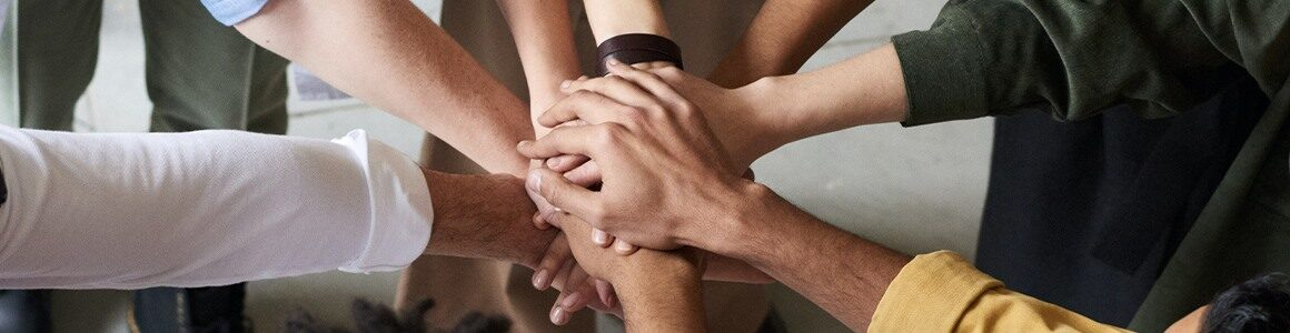 Diversity of people put their hands in together.