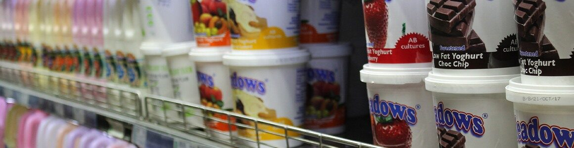 Dairy products with labels in a store fridge.
