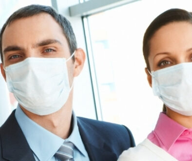 Two business men and two business women waring safety masks over nose and mouth.