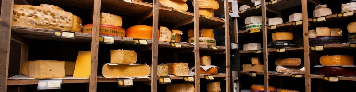 Wooden shelves stocked with variety of cheese.