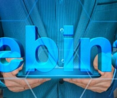 The word webinar in big blue font with man holding a tablet and an auditorium in the background.